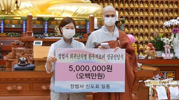 미산 정법사 김선정 신도부회장이 진여스님에게 성금을 전달하는 모습.